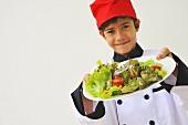 Junge als Koch hält einen Salatteller