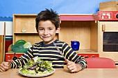 Junge mit einem Salatteller