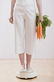 Young woman with carrots on bathroom scales