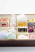 Various beauty products and flowers in type case