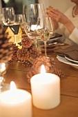 Weingläser und Kerzen am Weihnachtstisch, Frau im Hintergrund
