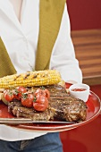 Woman holding T-bone steak, corn on the cob & cherry tomatoes