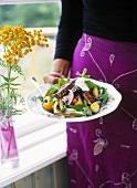 Frau hält Salatteller mit Rindfleisch