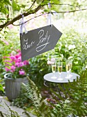 A placard hanging in a garden showing the way to a party