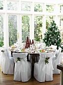 Festlich gedeckter Weihnachtstisch im Wintergarten mit Stühlen in eleganten Stoffhussen