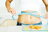 Young woman holding measuring tape around bare abdomen, plate of veggies in the foreground