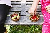Children sitting on a garden bench eating berries