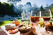 Men grilling food at family barbecue in summer garden, focus on food and wine on table in foreground