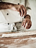 A chef dusting gnocchi dough with flour