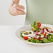 Hand hält Gabel über knackigem Salatteller