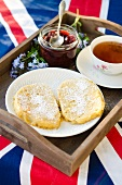 French toast, jam and a cup of tea on a wooden tray on top of a Union Jack flag