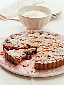 Linzer torte (nut and jam layer cake) with sliced almonds, partly sliced