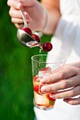 A woman pouring cherry cooler from a ladle into a glass
