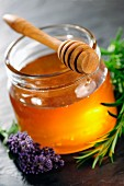 Honey jar with dipper, rosemary and lavender flower