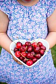A girl holding a heart-shaped dish of cherries