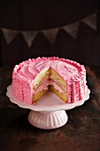 Raspberry layer cake on a cake stand, cut to show the inside
