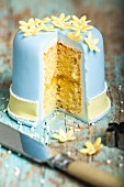 A layer cake iced with blue fondant and decorated with marzipan flowers, cut open to show the centre