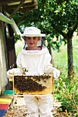 A girl holding a honeycomb covered in bees