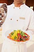 Koch hält einen Salatteller