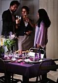 Gedeckter Weihnachtstisch mit violetter Tischdecke und Servietten mit silbernem Serviettenhalter; im Hintergrund drei Personen mit Weingläsern