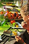 A girl eating tomatoes at a garden table in the summer