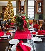 Festlich gedeckter Weihnachtstisch mit Blick auf leuchtenden Weihnachtsbaum im Wohnbereich