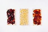Three crispbreads with jam and honey (seen from above)