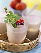 Berry milk shake in glasses on tray, spoon with berries above