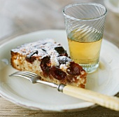 A piece of plum cake and a glass of apple juice
