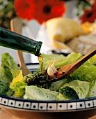 Öl aus Flasche auf Holzlöffel über Salatteller giessen