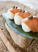 Sushi with salmon and capers on banana leaf