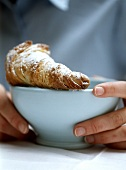 Hands holding bowl with croissant