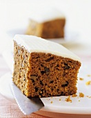 Piece of carrot cake with nuts and glacé icing