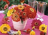Kleiner Blumenstrauss aus Zinnien in weisser Vase