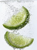 Lime wedges falling into mineral water