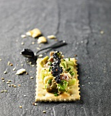 Black caviar, avocado and tuna on cracker