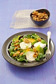 Salad leaves with goat's cheese, orange segments, walnuts and mint