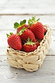 Several strawberries in small basket