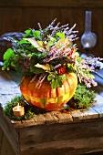 Kürbis als Vase mit herbstlichem Blumenstrauss