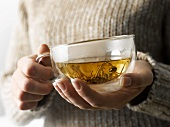 Woman holding a cup of jasmine tea in her hands