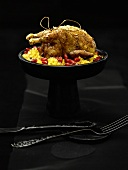 Quail with gold leaf on couscous with pomegranate seeds