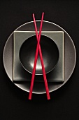 Black plates and bowl and red chopsticks (overhead view)