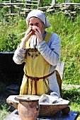 Girl in Viking costume drinking out of terracotta bowl