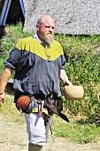 Man in Viking costume carrying water bowl
