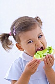Little girl eating cucumber, quark and chives on bread