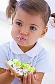 Little girl eating slice of bread with quark, cucumber and radishes