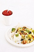 Pasta salad with tomatoes, olives, pine nuts and feta