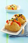 Baked potatoes with tomato and olive salad