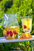 Iced tea with raspberries in a jug and a glass on a garden table