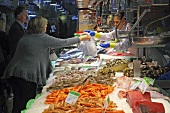 Customers at a fish and seafood market stall (Mercat de St. Josep (Boqueria), Las Ramblas, Barcelona, Spain)